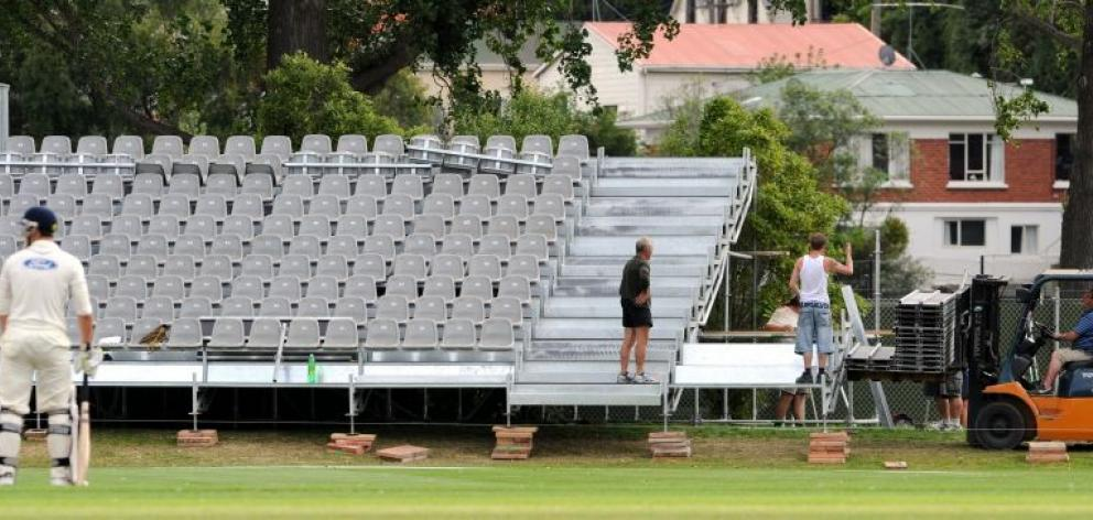 Workers assemble temporary seating for the test between New Zealand and England at the University Oval next month. Photo by Craig Baxter.