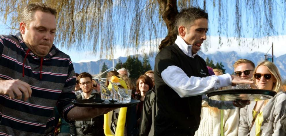 Frazer Currie (Queenstown Resort College), left, and Diego Moyano  (St Mortiz)  concentrate in the Queenstown Winter Festival waiters' race yesterday. Photo by Stephen Jaquiery.