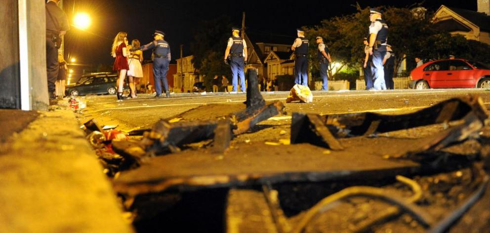 Police officers move revellers off Castle St, Dunedin, where about 300 people gathered around two couch fires on Saturday night. Photo by Craig Baxter.