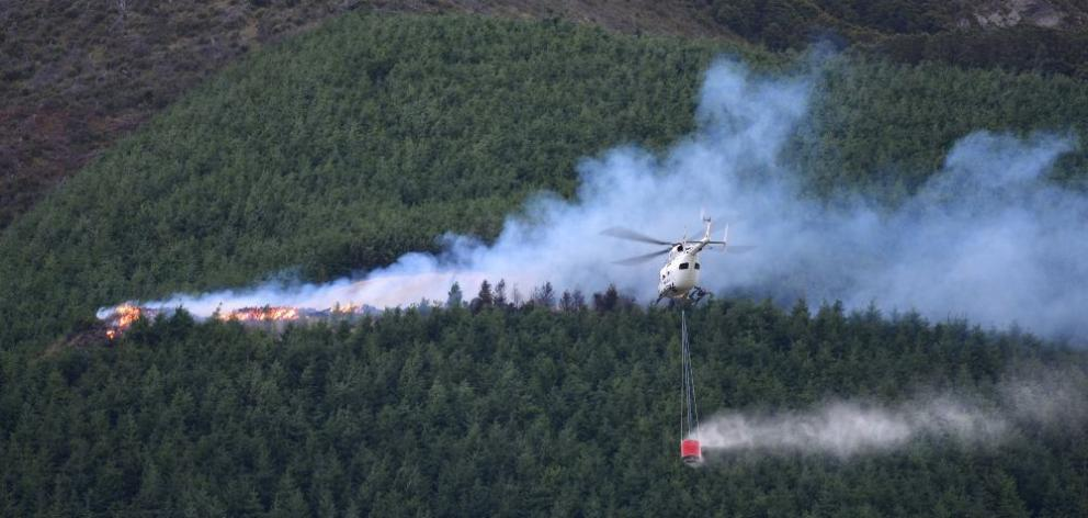 A Helicopters Otago chopper piloted by Roger Cochrane flies in to  drop more  water  on the Blue Mountains forest fire on Wednesday. Photo by Stephen Jaquiery.
