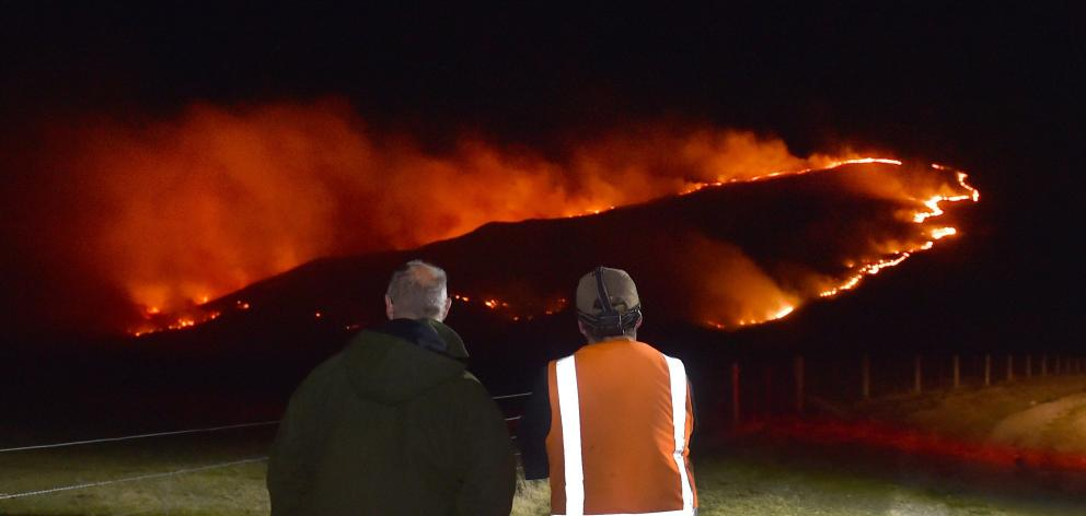 Onlookers watch as a fire rages in the Rock and Pillar Range above Middlemarch last night. Photo: Peter McIntosh