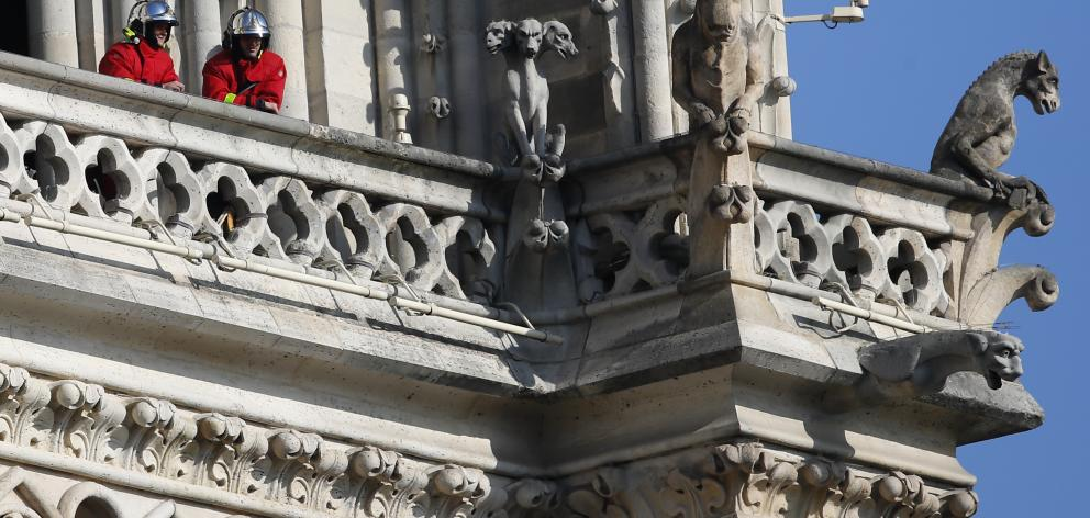 Firefighters at a balcony of the cathedral where gargoyles watch over Paris. Photo: AP