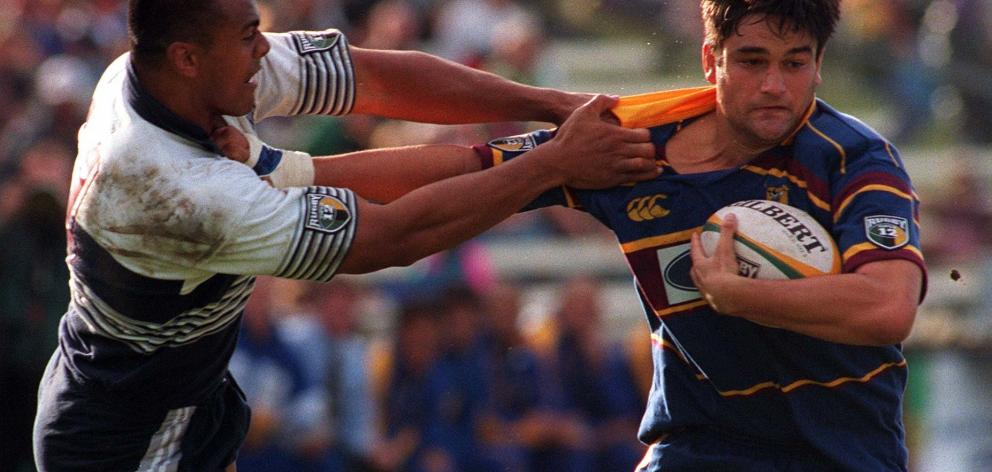 Highlanders loose forward Taine Randell attempts to fend off the tackle of Blues wing Jonah Lomu...