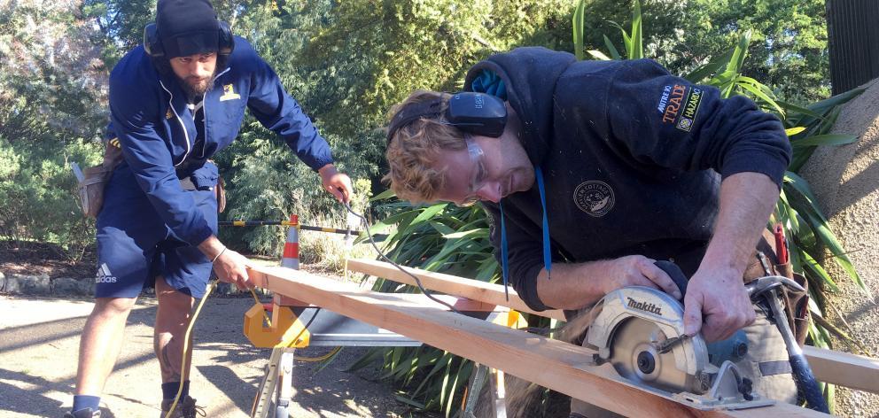 Highlanders loose forward Jackson Hemopo (left) helps Seaview Cottage Construction senior foreman...