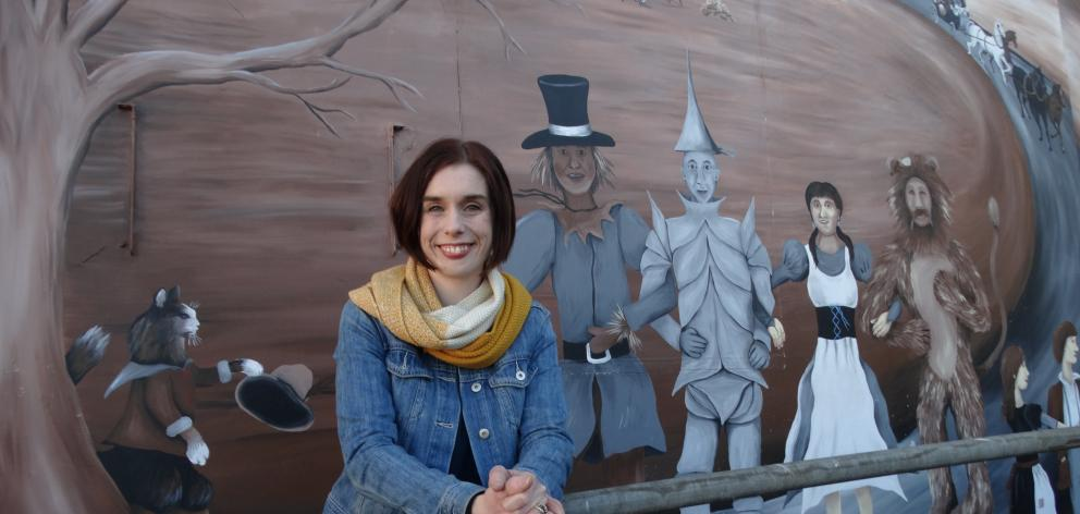Dunedin Repertory Society vice-president Jemma Adams is flanked by the giant mural of characters...