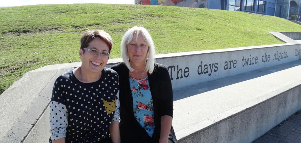 Poems in the Waiting Room co-ordinator Ruth Arnison (left) and artist Sheryl McCammon enjoy the poem Dunedin Summer, by the late Jean Lonie, which adorns the concrete seating/steps in front of the South Coast Boardriders clubrooms at St Clair.