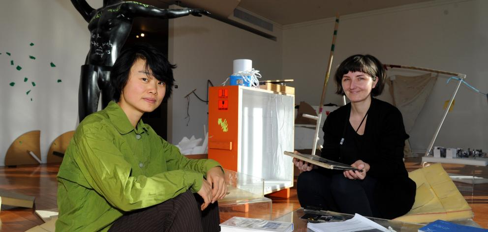 Auckland artist Xin Cheng and Dunedin Public Art Gallery curatorial intern Andrea Bell discuss the exhibition, surrounded by rejected items they hope people will use to create new things. Photo by Chris O'Connor.
