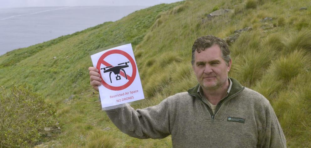 Taiaroa Head Department of Conservation ranger Lyndon Perriman holds a no fly zone sign that have...