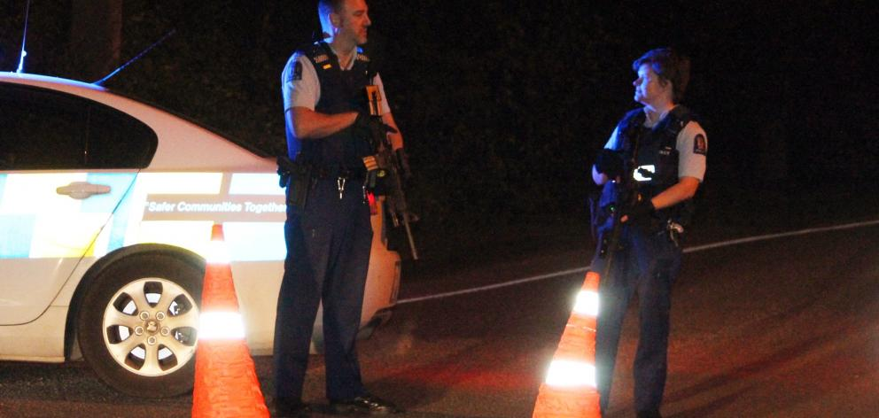 Armed police officers stop traffic at the intersection of Dunns and Otatara Rds on the outskirts...