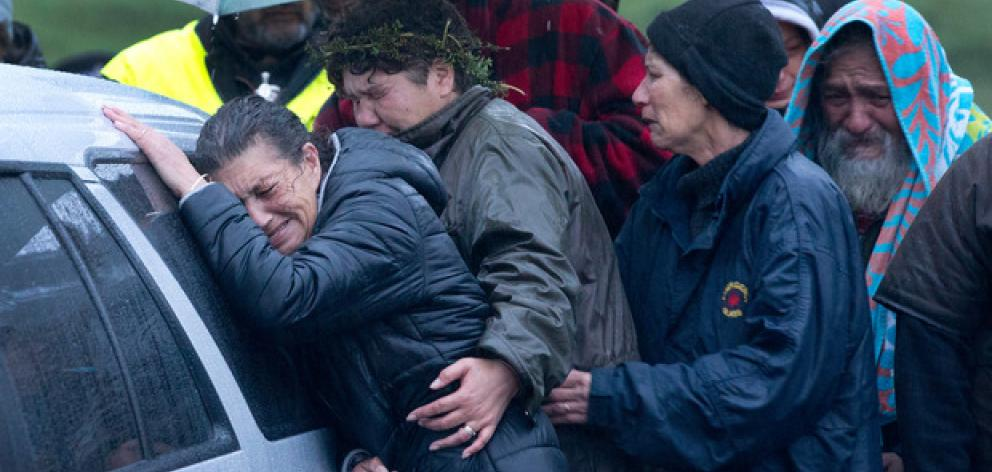 Friends and family mourn as the bodies of two people found dead in the tiny settlement of...
