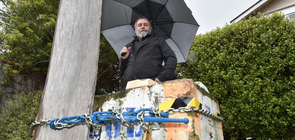 Richard Healey inspects  a power pole secured to a concrete block in Farley St yesterday ...