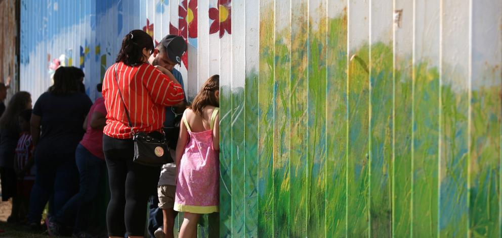 People talk to relatives at the border wall  dividing the US and Mexico in Tijuana. Photo: Reuters