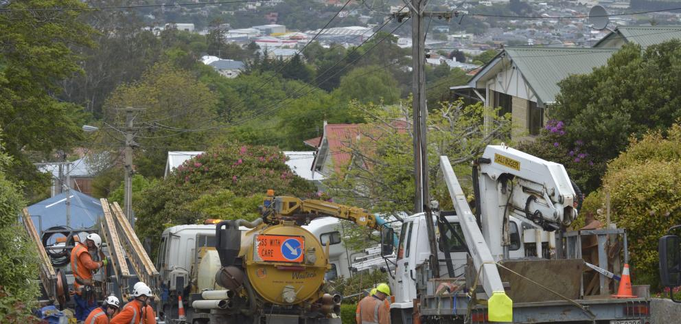 Linemen work to replace a red-tagged pole in Argyle St, Mornington, after it was struck by a...
