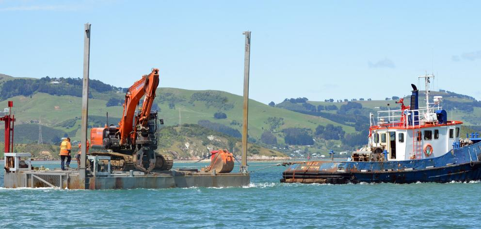 Port Otago work boat Kapu tows a digger on a barge to Port Chalmers on Thursday after another ...