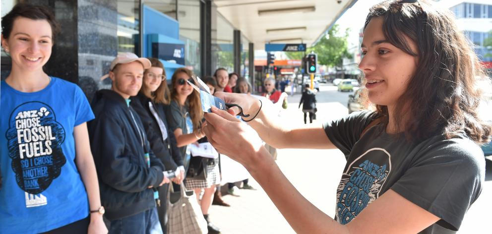 Claudia Palmer (20) cuts her ANZ eftpos card in half to protest against the bank's investments in...
