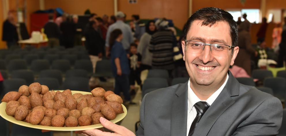 Otago Syrian Association president Ghassan Idris holds up a plate of kibbeh at a potluck for refugees at Carisbrook School on Monday night. Photo by Peter McIntosh.