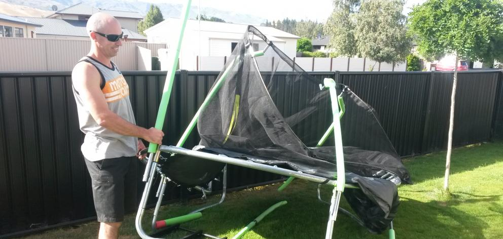 Nathan Manning, of Cromwell, helps move a trampoline destroyed by a tornado at his friend's house...
