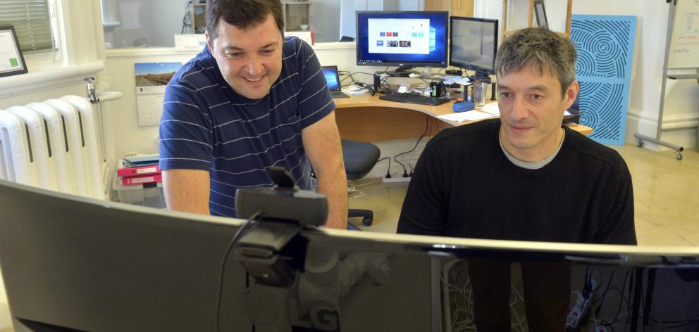 Greg Peyroux (left) and Benoit Auvray examine a model at their Iris Data Science office this week...