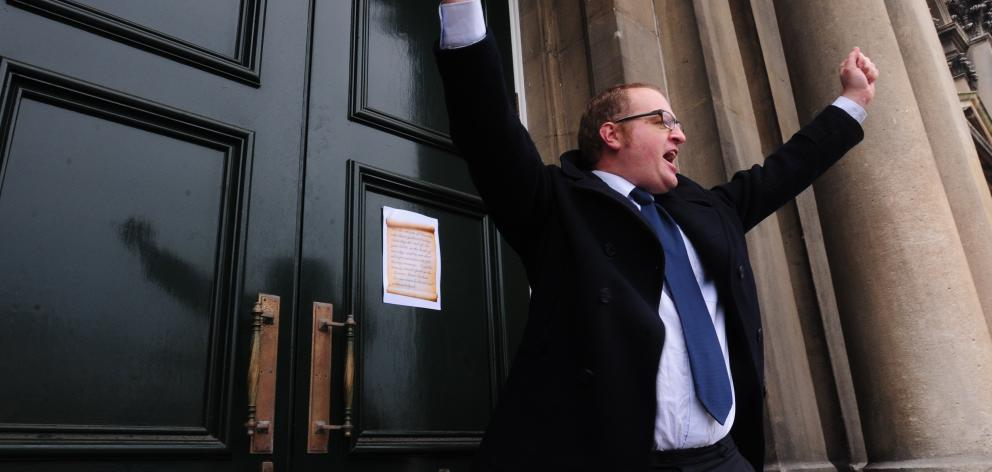 Victor Billot gestures after pinning a message to the doors of Dunedin's Municipal Chambers as...