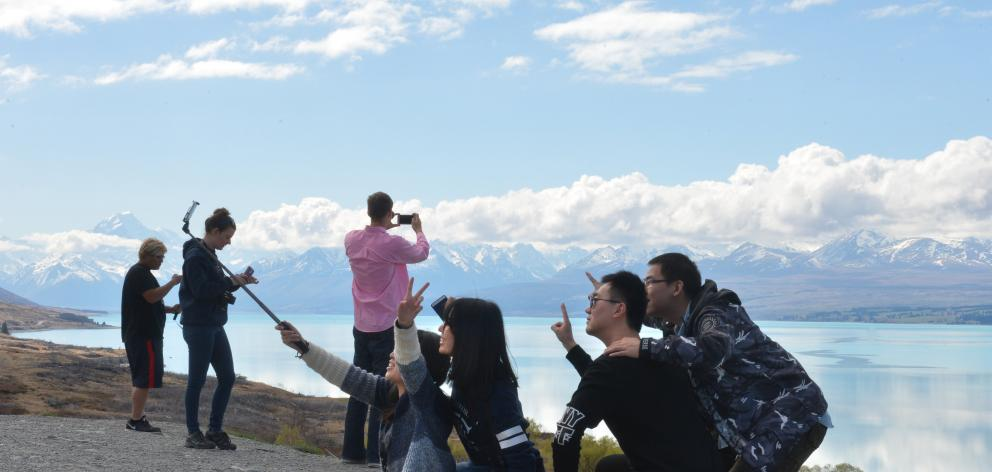 Some of the nearly 3.5 million visitors to New Zealand last year take selfies and photographs on the shores of Lake Pukaki. Photo by Stephen Jaquiery.