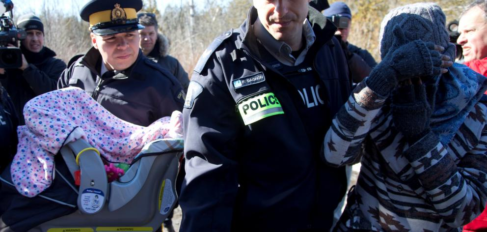 A mother and child are taken into custody by Royal Canadian Mounted Police after crossing the US...