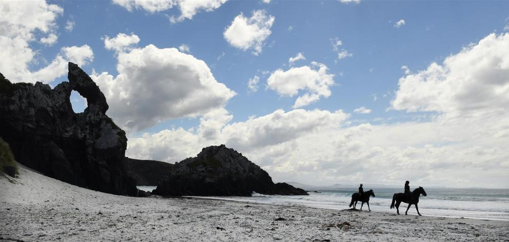 Cheryl Mangan (left) and Eli Cumming ride past Keyhole Rock at Aramoana yesterday, as the Dunedin City Council considers new rules for horses on the city's beaches. Photos by Peter McIntosh.