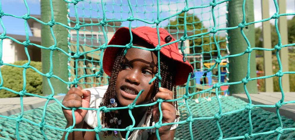 Pupil Oluwafikunayomi Agbowuro (4) looks at damage to side netting on a fort structure at...