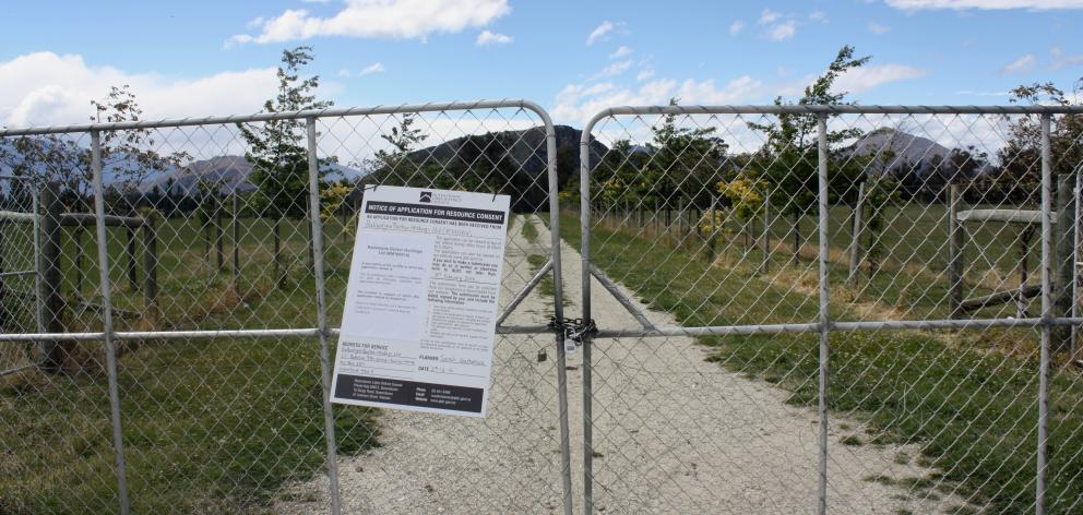 A Queenstown Lakes District Council notice of application for resource consent hangs on the gate...