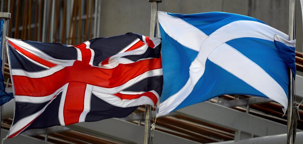 A Saltire, and Union Jack flags flutter in the wind outside the Scottish Parliament on March 13, 2017 in Edinburgh, Scotland. Getty