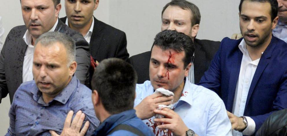 An injured leader of the Social Democrats Zoran Zaev is escorted out of the parliament in Skopje. Photo: Reuters