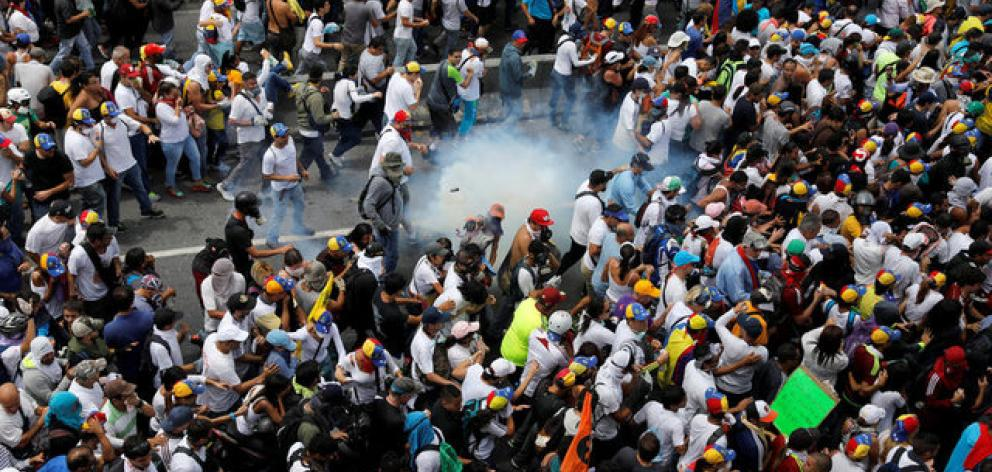"Demonstrators clash with riot police during the so called ""mother of all marches"" against Venezuela's President Nicolas Maduro in Caracas. Photo: Reuters"