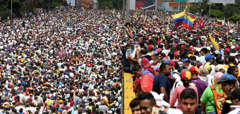 Crowds swelled to hundreds of thousands, including Maduro supporters who held a counter-demonstration in the capital. Photo: Reuters