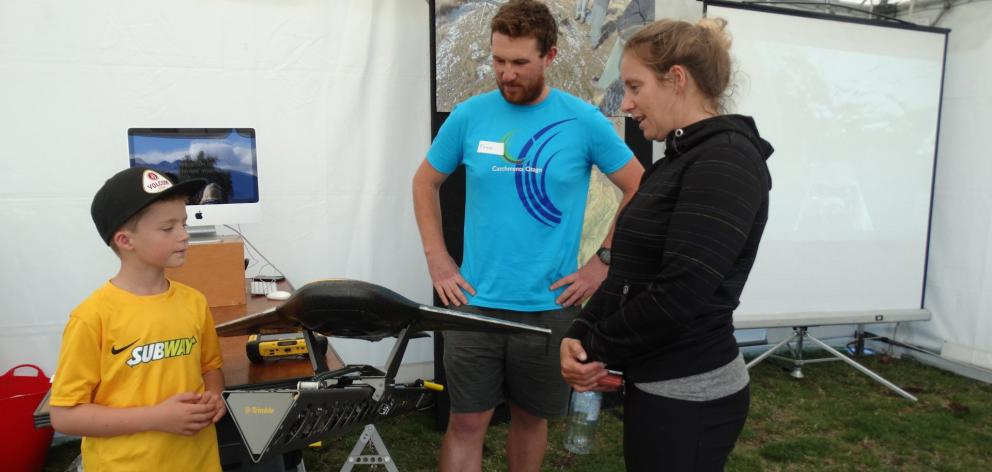 Otago University PhD student Todd Redpath shows Jai (7) and Ashela Jackson, of Wanaka, a fixed-wing drone used to survey snow depths, at a Lab at the Lake family fun day on Sunday. Photo by Kerrie Waterworth.