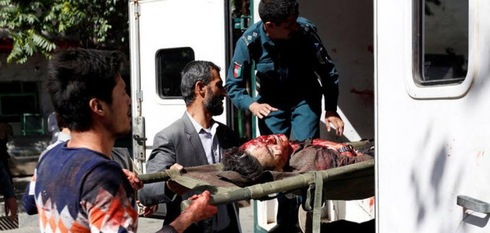 Men move an injured man to a hospital after a blast in Kabul, Afghanistan. Photo: Reuters