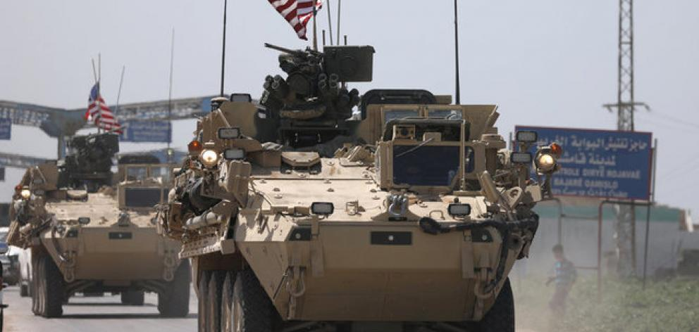 US military vehicles travel in the northeastern city of Qamishli, Syria. Photo: Reuters
