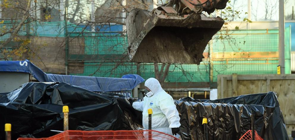 Workers in protective suits remove asbestos from the Great King St site where the University of...