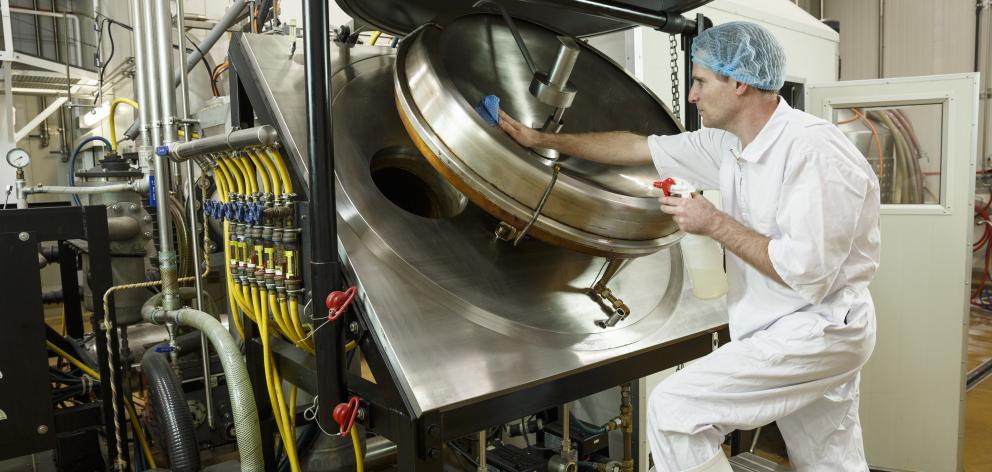 A SeaDragon technician cleans fish oil refining equipment.