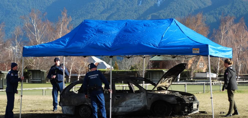 Police examine the burned-out car in Queenstown's Jardine Park yesterday. PHOTO: GUY WILLIAMS