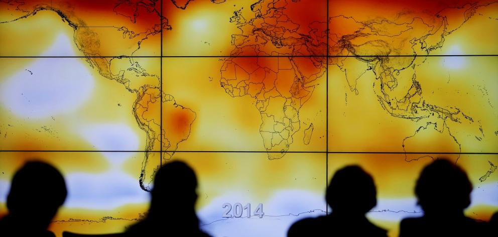 Participants look at a screen showing a world map with climate anomalies during a World Climate...