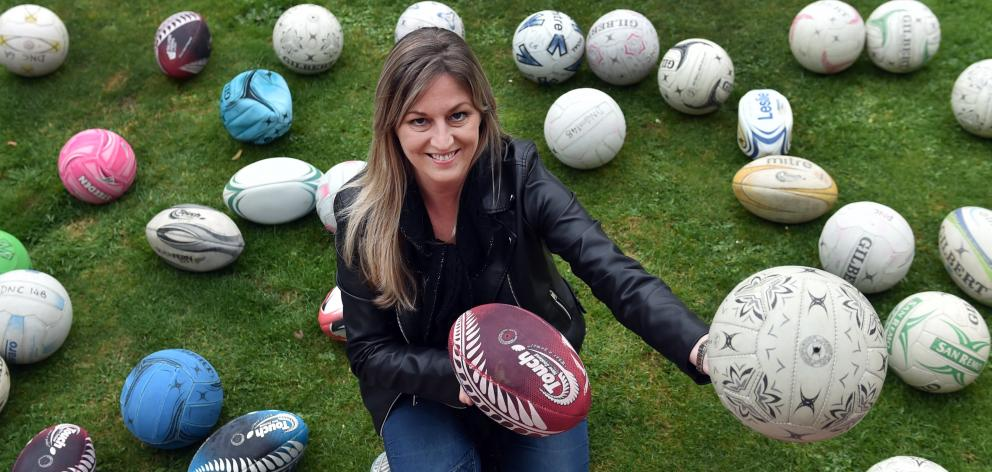 Otago Polytechnic student Carla Hore displays part of a donated collection of used sports balls....