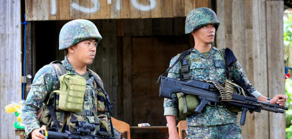 Soldiers stand guard along the main street of Mapandi village as government troops continue their assault on insurgents from the Maute group. Photo: Reuters