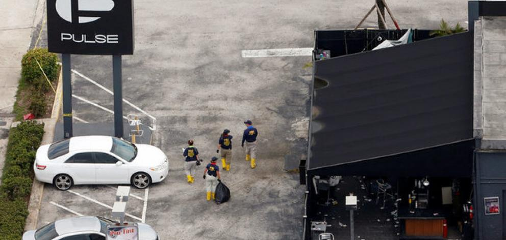 Federal Bureau of Investigation (FBI) officials walk through the parking lot of the Pulse gay night club, the site of a mass shooting days earlier, in Orlando, Florida. Photo: Reuters