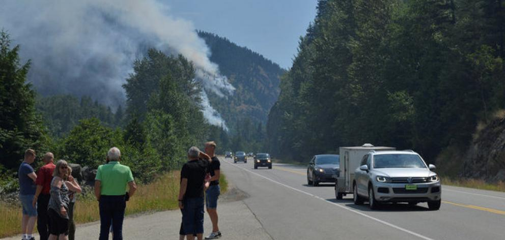 Tourists from Denmark stop to photograph one of several wildfires burning near Little Fort,...