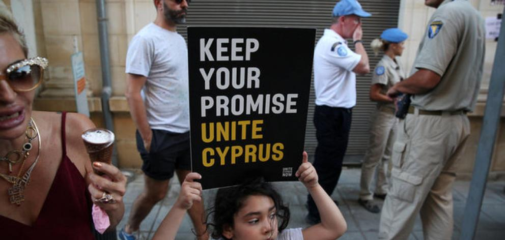 A girl holds a placard during a demonstration in favour of a peace settlement between Greek and Turkish Cypriots on divided Cyprus. Photo: Reuters