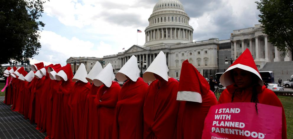Women dressed as handmaids from the novel, film and television series The Handmaid's Tale...