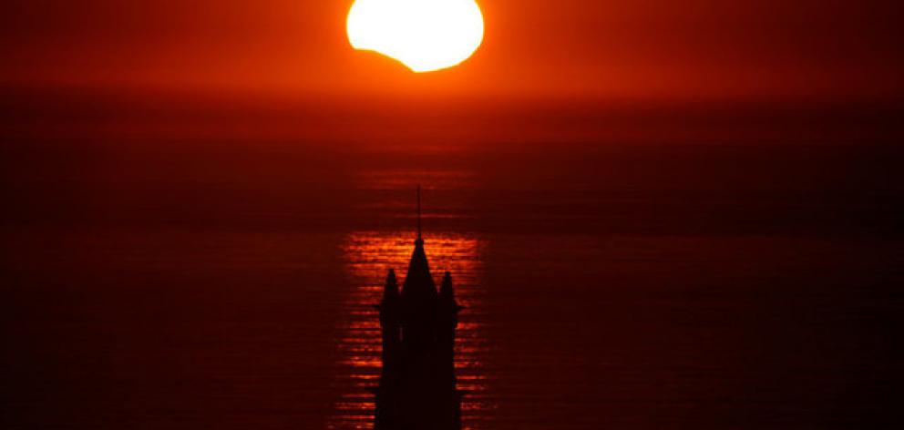 The Saint-They Chapel is seen in silhouette at sunset during a partial solar eclipse as the moon passes in front of the sun. Photo: Reuters