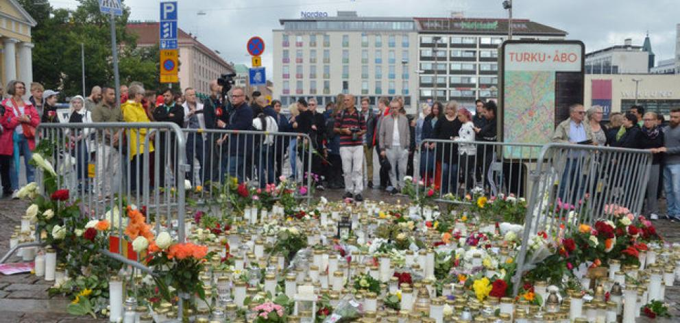People mourn next to memorial candles and flowers at the Market Square in Turku. Photo: Reuters