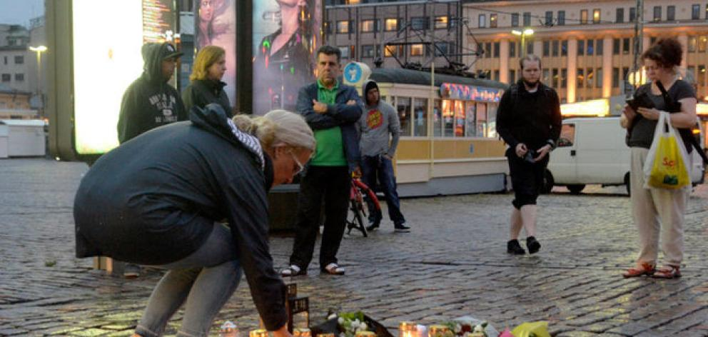 A woman puts candle at the Market Square where several people were stabbed, in Turku. Photo: Reuters