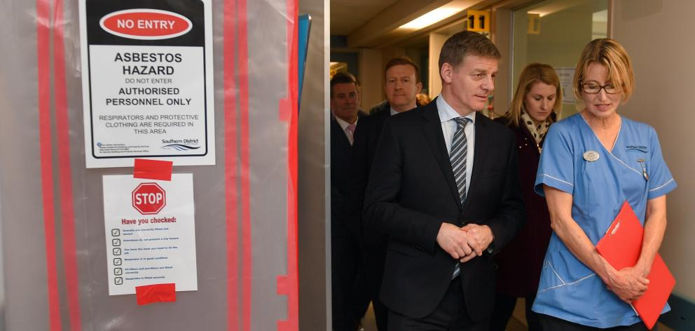 Prime Minister Bill English walks with charge nurse Mary Molloy past an asbestos warning sign at...