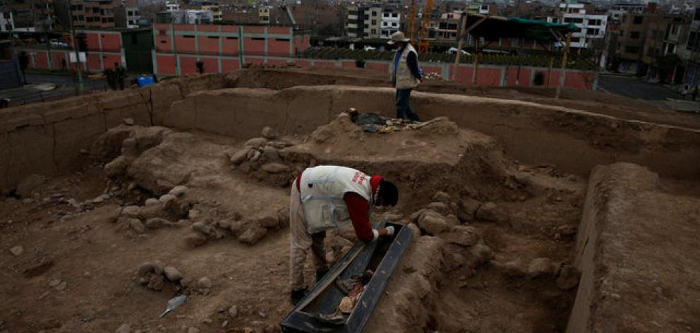 Archaeologist works at a tomb of one of sixteen Chinese migrants, discovered buried at the turn of the 20th century in the pre-colombian pyramid of Bellavista in Lima. Photo: Reuters